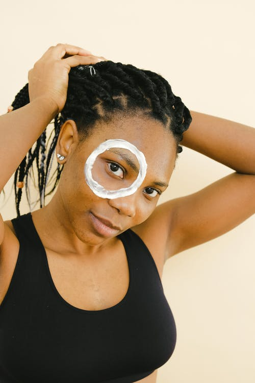 Young African American female in black sports bra and with cream around one eye collecting pigtails and looking at camera