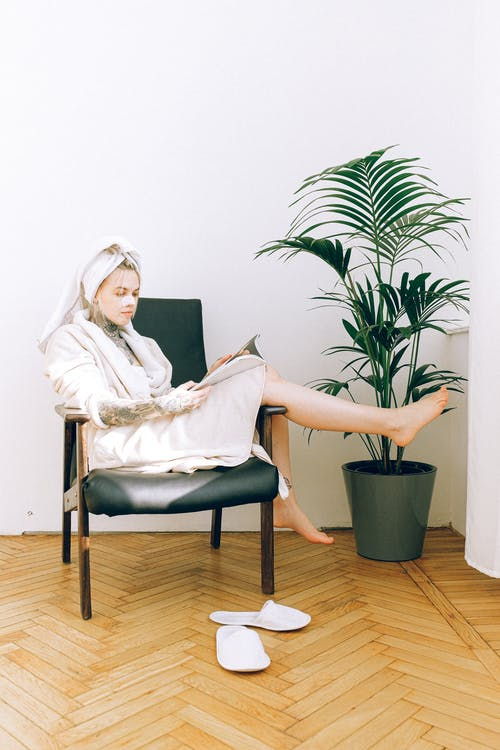 Woman in robe and cosmetic mask reading magazine Better Skin - While Working from Home