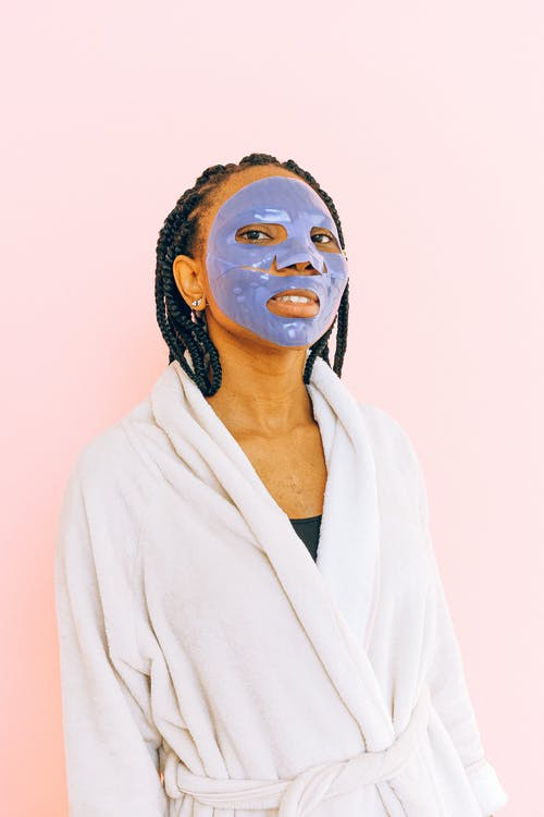 African American woman in bathrobe and blue cosmetic mask