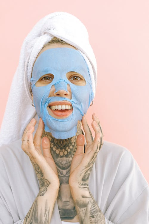 Happy woman applying collagen mask after taking bath