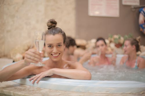 Cheerful friends with glass of champagne sitting in jacuzzi