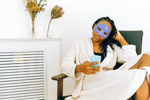African American woman in bathrobe and cosmetic mask watching smartphone