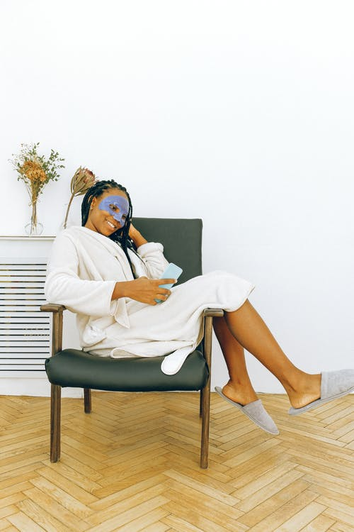 Young cheerful black woman relaxing with smartphone during facial treatment at home