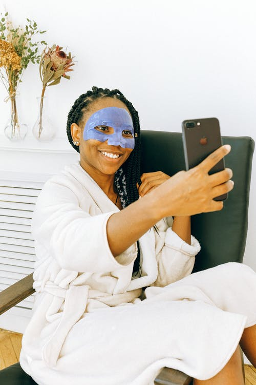 Young black woman in blue facial treatment mask using smartphone at home