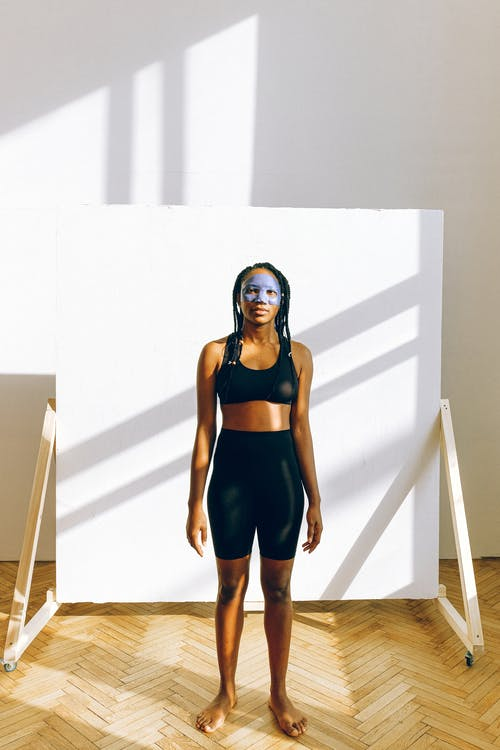 Full body confident African American female with braided long curly hairstyle wearing sport bra and leggings standing against white backdrop in minimal interior room with white wall and wooden parquet floor and looking at camera