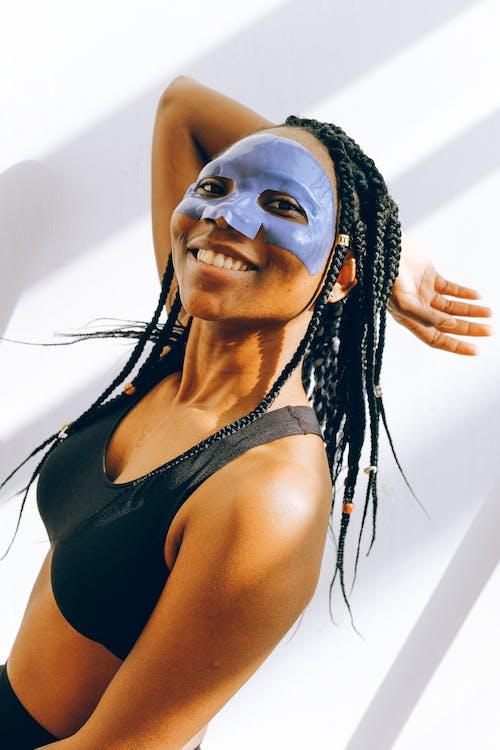 Woman in Black Tank Top Wearing Purple Face Mask