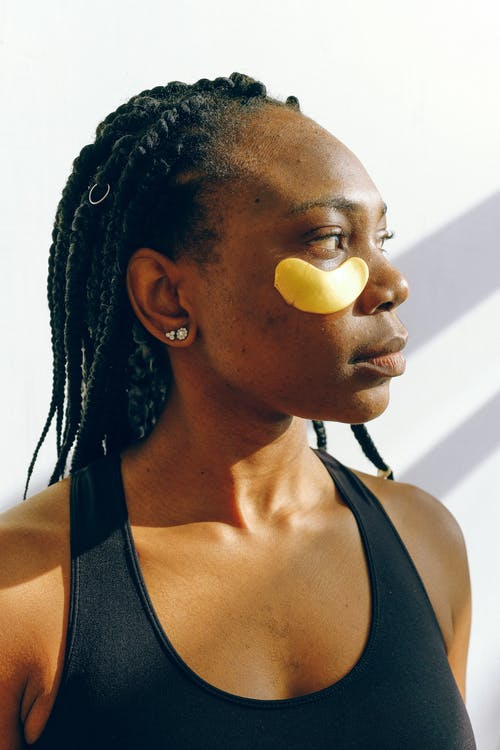 Young black woman with golden patches under eyes during cosmetic procedure