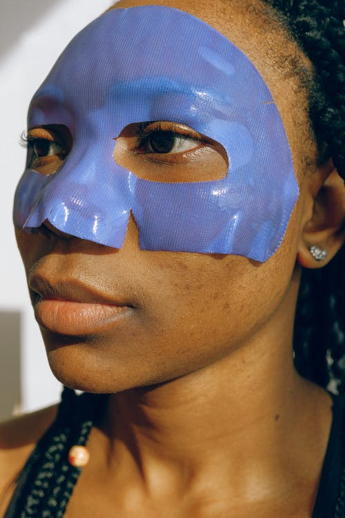 Portrait Photo of Woman Wearing Purple Face Mask