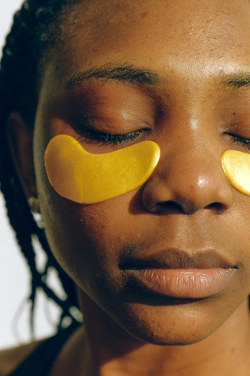 Young peaceful black woman applying golden collagen eye patches