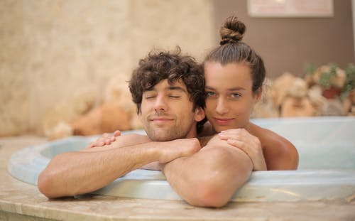 Young cheerful man and woman taking bath together enjoying holidays on blurred background of spa resort with marble interior and having romantic moments