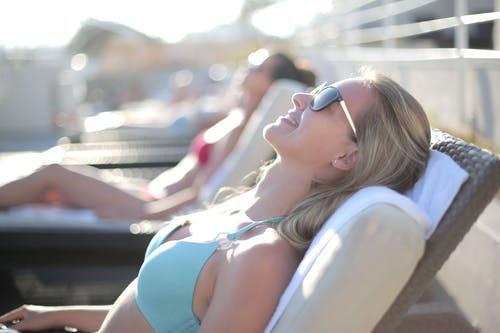 Selective Focus Photo of Woman in Teal Brasserie Wearing Sunglasses Relaxing on Pool Chair