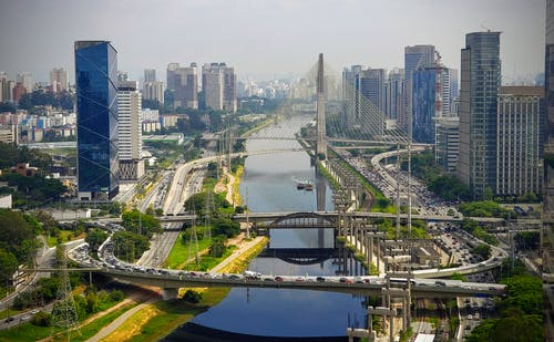 Amazing view of modern urban district in Sao Paolo with futuristic bridge and constructions over river during clear day