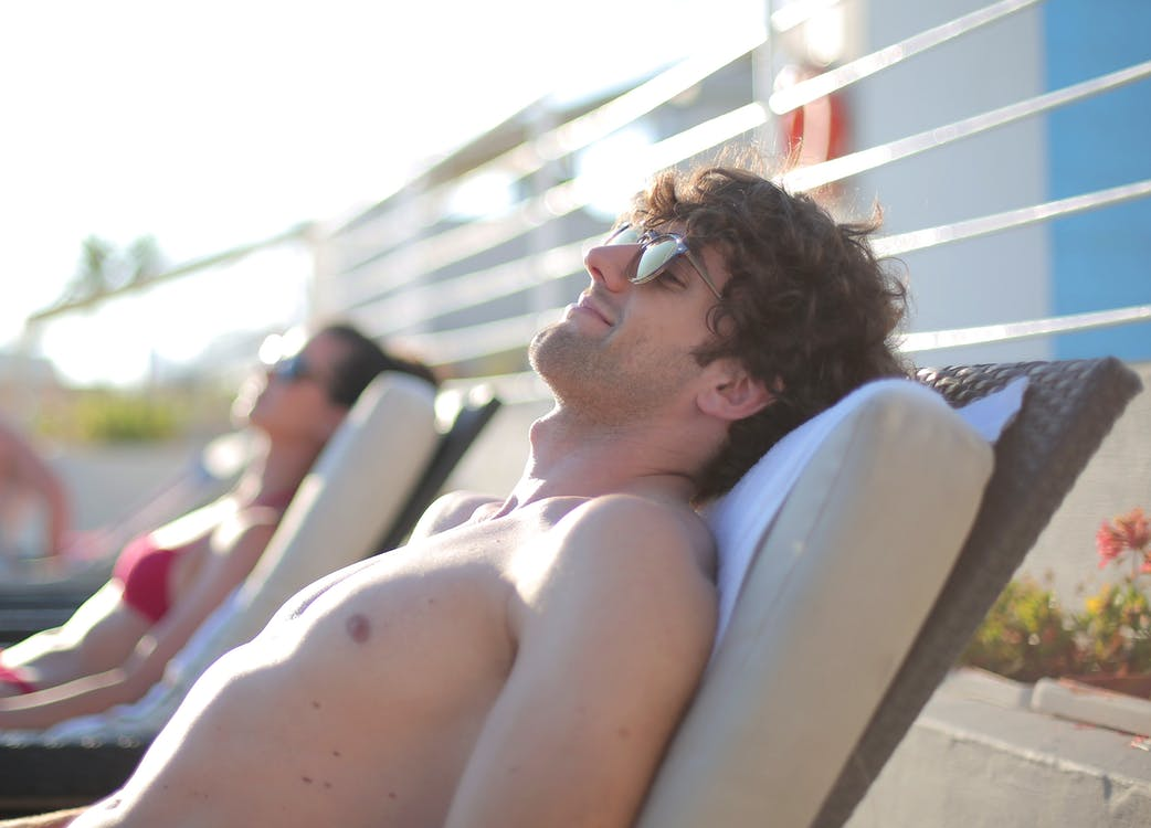 Smiling man and female in sunglasses and swimsuits sunbathing while chilling together on deckchairs near pool on sunny day