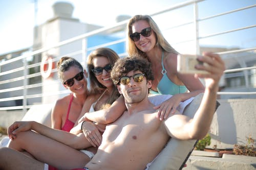 Cheerful young people wearing swimwear and sunglasses taking photo on mobile phone while chilling together on seafront in morning