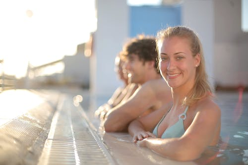 Happy blond female in swimwear smiling at camera while resting on poolside and spending time with friends on sunny day