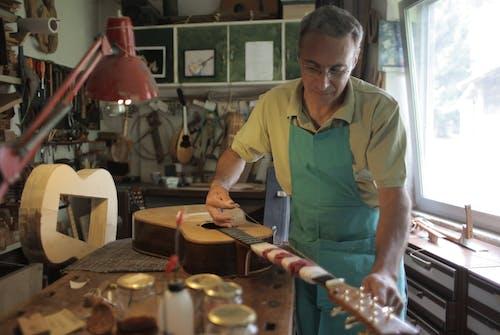 Senior craftsman mending guitar in workshop