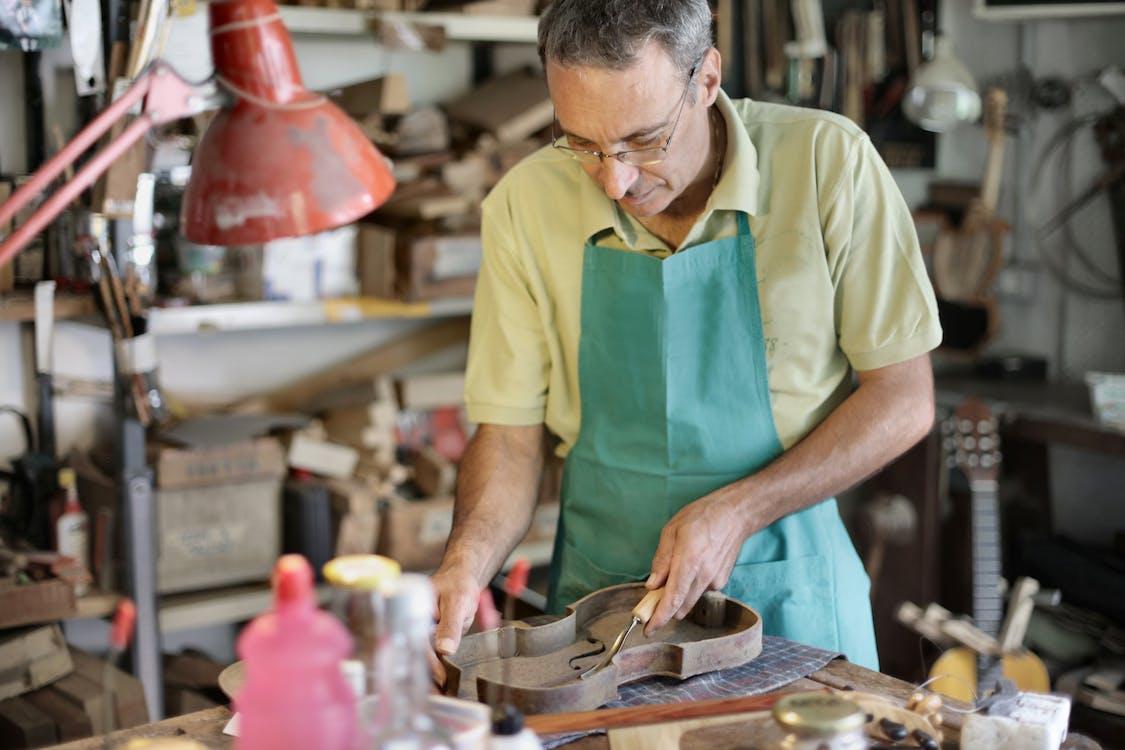 Senior artisan working with wooden details in workshop
