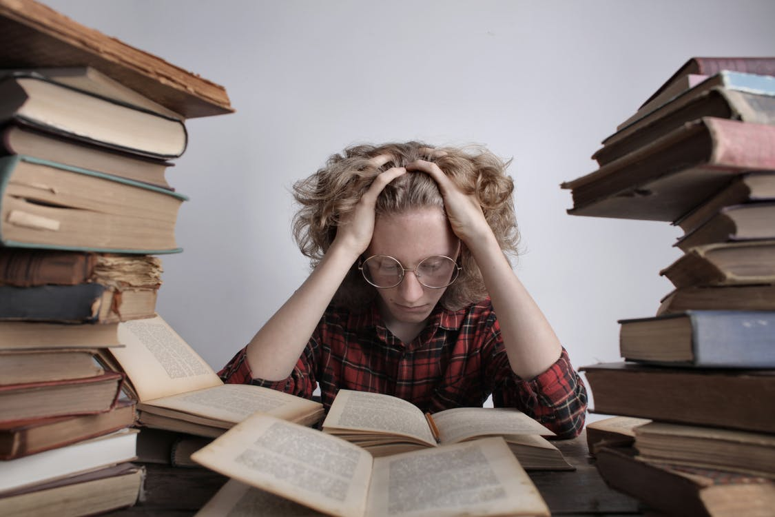 Tired teenage boy in casual clothes and eyeglasses sitting at desk with large stacks of books holding head and reading book while preparing for exam