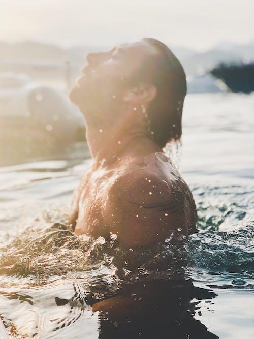 Bearded man swimming in pool water in sunlight