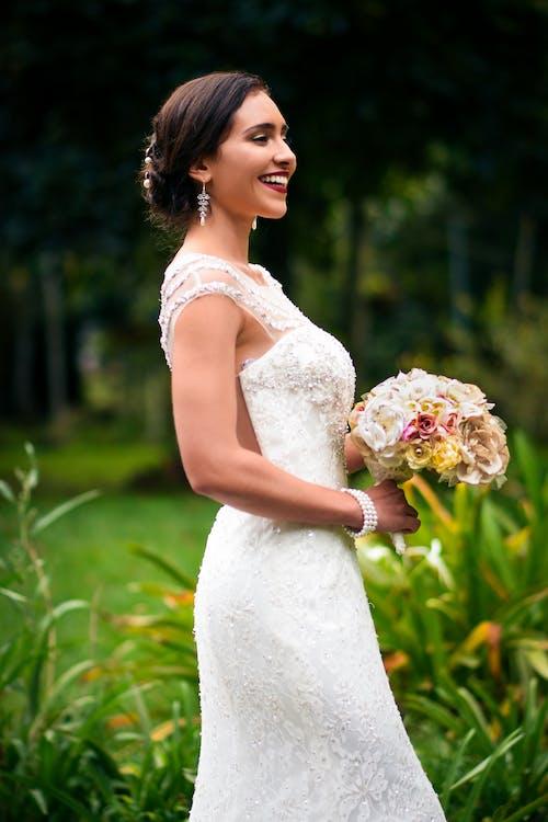 Frau Im Weißen Blumenhochzeitskleid Mit Blumenstrauß Lächelnd
