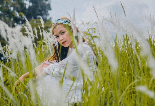 Young Asian woman sitting on grassy meadow