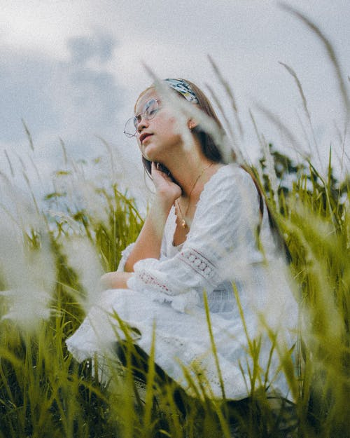 Dreamy Asian woman resting on grassy lawn