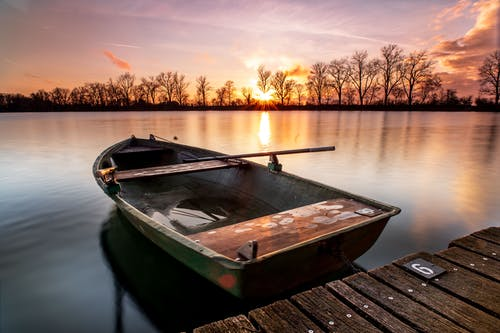 Brown Wooden Boat on Dock during Sunset