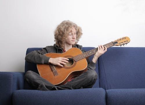 Man in Gray Hoodie Playing Brown Acoustic Guitar