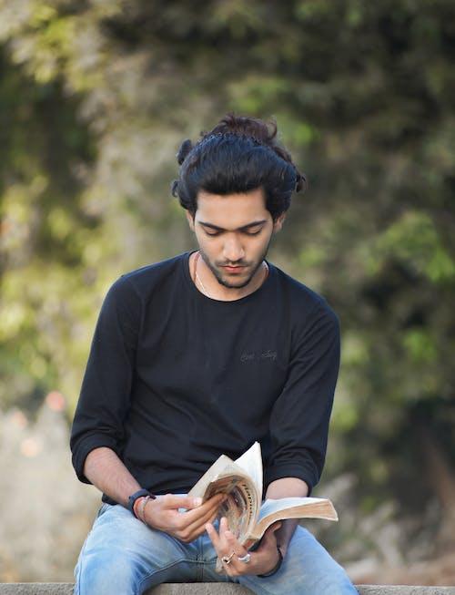 Man in Black Long Sleeve T-shirt Reading Book