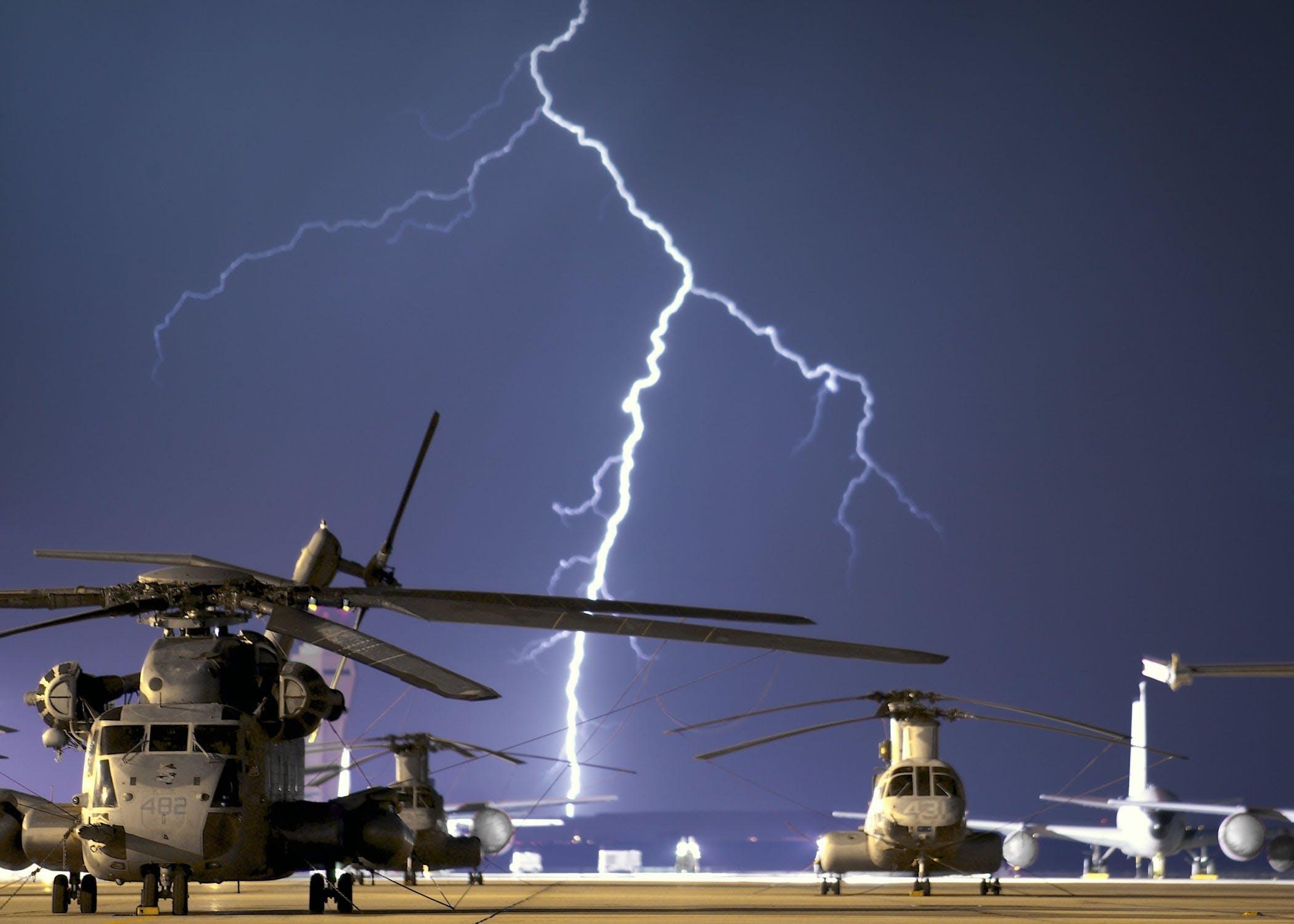 Lightning Near Grey Helicopter during Daytime