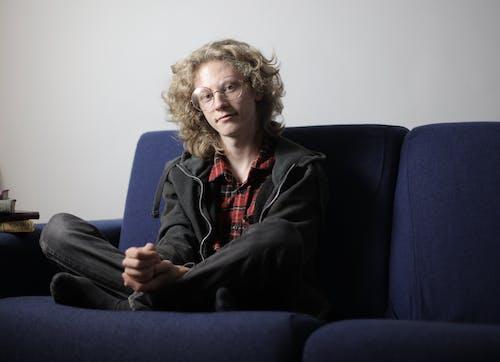 Pleased teenager sitting on sofa