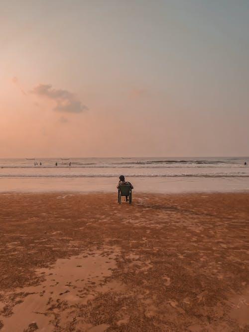 Anonymous person on wheelchair enjoying sunset on seashore