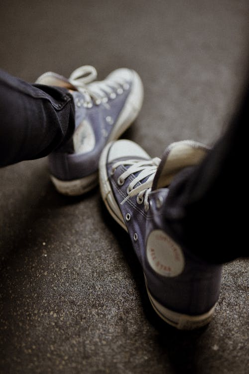 Person Wearing Blue Denim Jeans and White Converse All Star High Top Sneakers