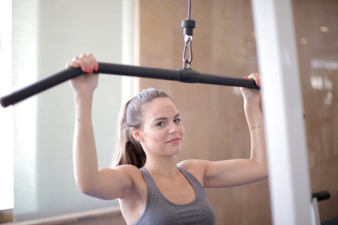 Young friendly muscular woman in sports bra doing exercises using training apparatus and looking at camera during arm training in fitness center