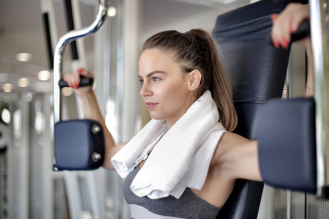 Confident sportswoman doing exercise on training apparatus