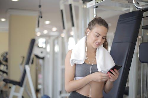 Joyful sporty female in earphones browsing smartphone