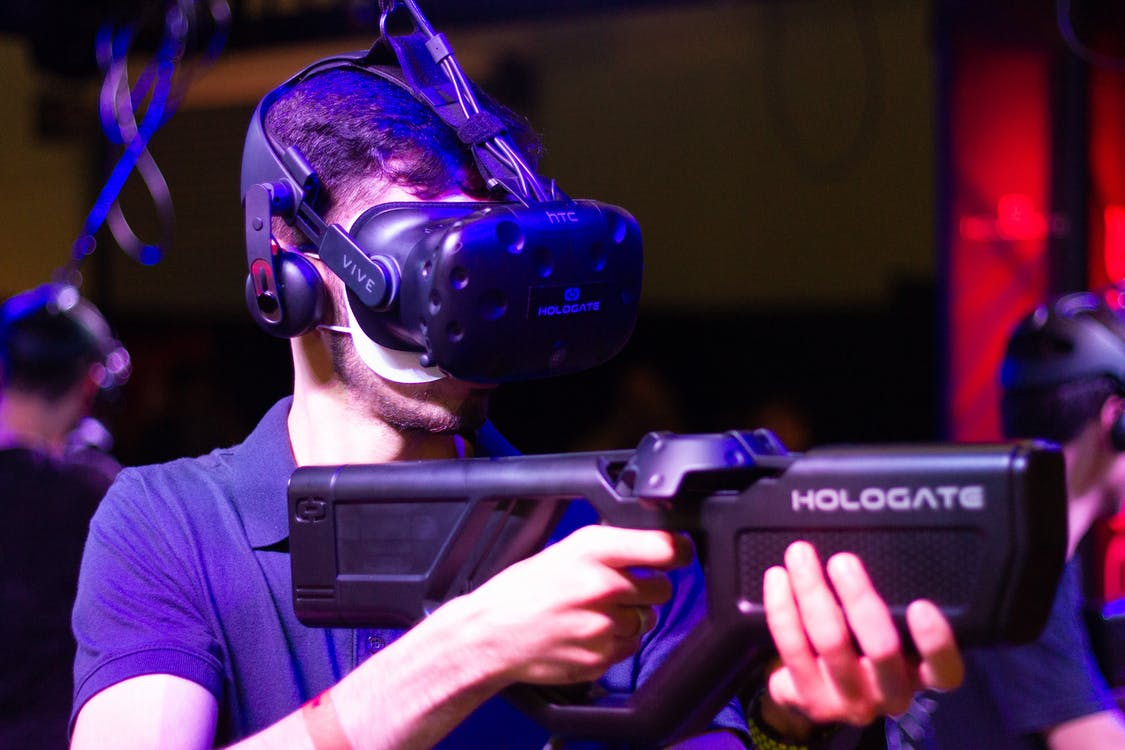 Man in VR with game riffle playing video game