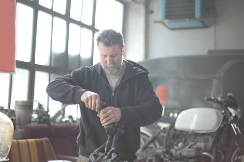 Bearded man repairing motorcycle in workshop