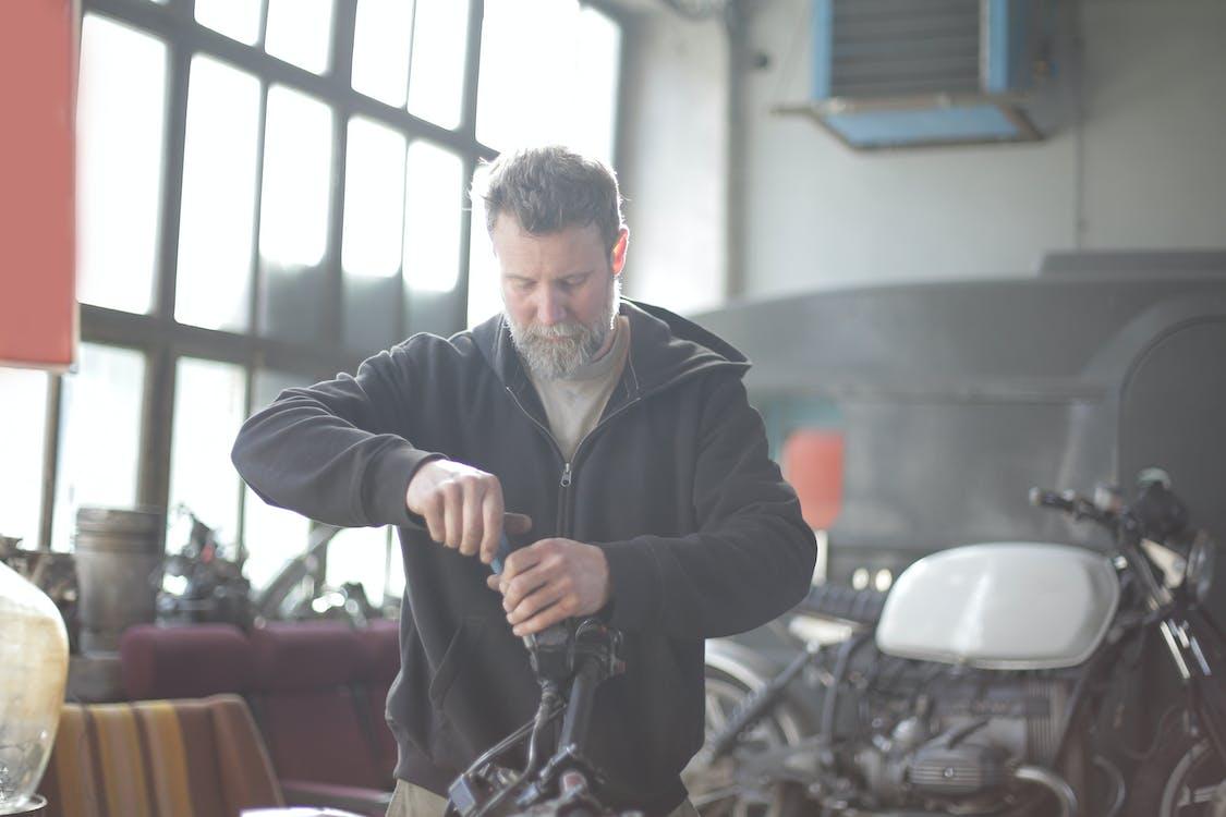Bearded man repairing motorcycle in workshop