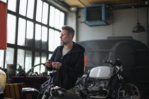 Side view of bearded man in casual wear standing in auto service holding detail in hand and looking away while repairing motorbike