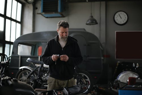 Focused adult bearded male mechanic in workwear standing with details in spacious garage near motorbike and looking down