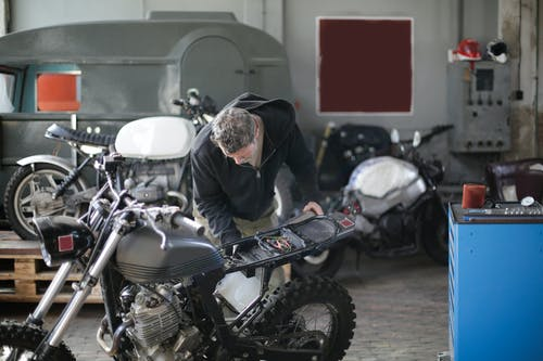 Middle aged bearded male mechanic in workwear and repairing motorbike while standing in modern spacious garage