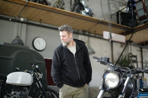 Serious adult male mechanic standing in garage near motorbike