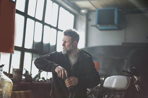 Confident bearded male mechanic working in modern garage