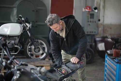 Serious adult male mechanic repairing motorbike in garage