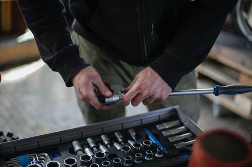 Unrecognizable crop adult male mechanic in black workwear installing metal socket on ratchet while working in modern workshop