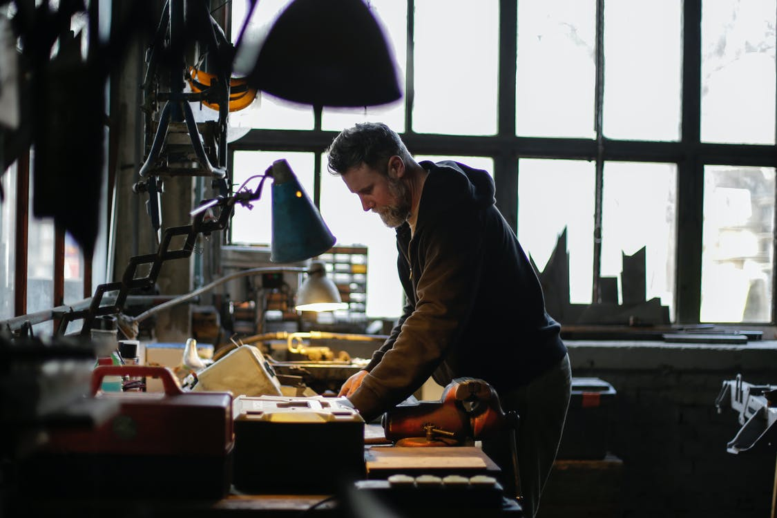 Side view of serious adult bearded male mechanic in workwear standing near workbench and working with details of engine in light of lamp in garage