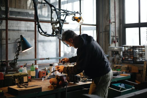 Back view of unrecognizable male mechanic in workwear standing near workbench while fixing broken metal detail in lamplight in modern workshop