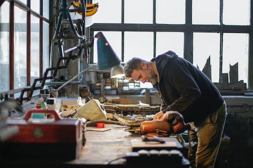 Adult male mechanic fixing metal detail in workshop