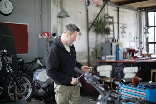 Side view of serious middle aged male mechanic in workwear standing with ratchet in modern garage while repairing motorbike
